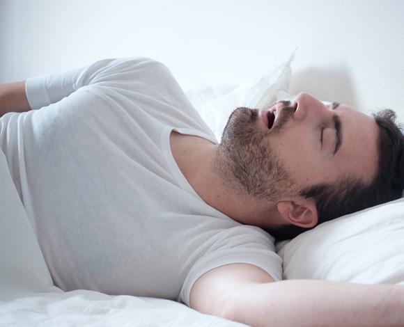 Mann sover med munn åpen